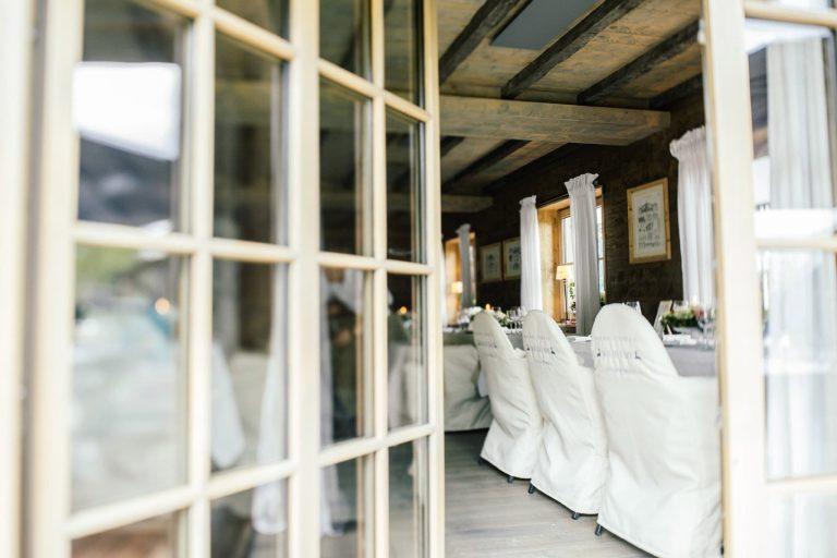 BLick in den feierlichen Saal Alm Chalet mit weißen Stühlen Relais Chalet Wilhelmy