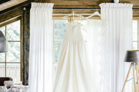 Brautkleid am Fenster des Alm Chalet für Hochzeit Relais Chalet Wilhelmy