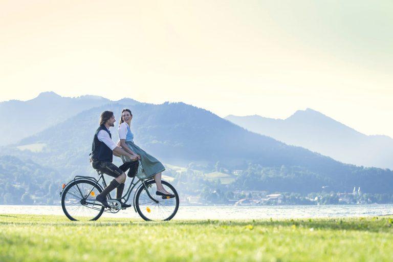 Glückliche Momente am Tegernsee im Relais Chalet Wilhelmy verliebtes Paar auf dem Rad
